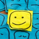 A yellow smiling post-it note in amongst unhappy blue ones